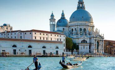 Gondoliers on gondola at Grand Canal in Venice. Basilica Santa Maria della Salute in sunny day